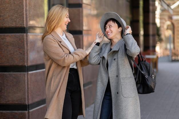 Hermosas mejores amigas de mediana edad pasar tiempo juntos en la ciudad