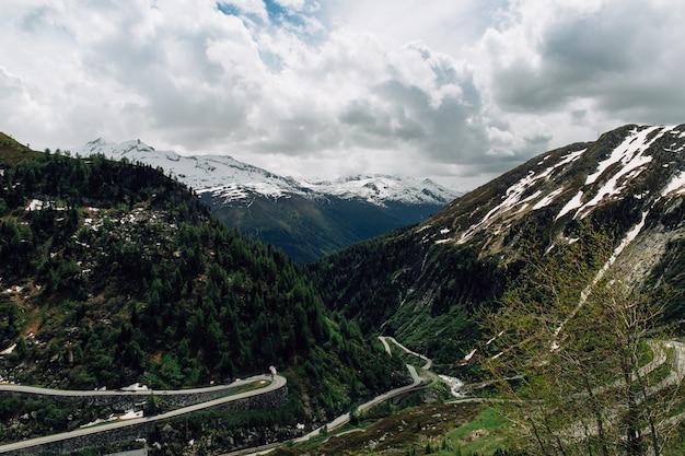 Hermosas montañas nevadas de los alpes suizos y pista curva en verano
