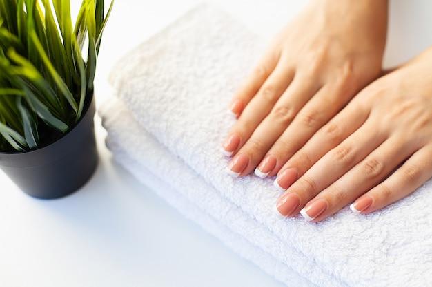 Hermosas uñas de mujer con manicura francesa, en estudio de belleza