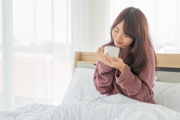 Hermosas mujeres asiáticas bebiendo café en la cama por la mañana