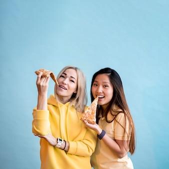 Hermosas mujeres asiáticas comiendo pizza