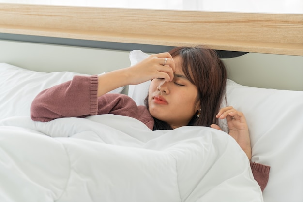 Hermosas mujeres asiáticas dolor de cabeza y durmiendo en la cama