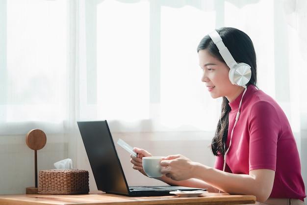 Hermosas mujeres asiáticas que trabajan en línea en casa. ella es freelance de ventas en línea, disfruta trabajar en casa