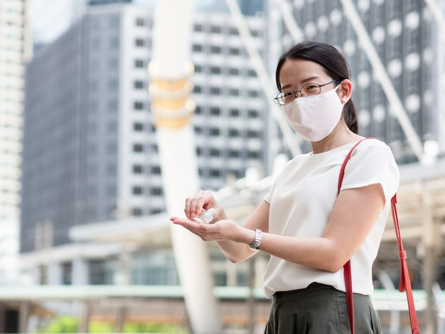 Hermosas mujeres asiáticas que usan mascarilla médica, usan gel de alcohol o desinfectante para limpiarse las manos mientras están en un área pública o centro de la ciudad, como una nueva tendencia normal y autoprotección contra la infección por covid19