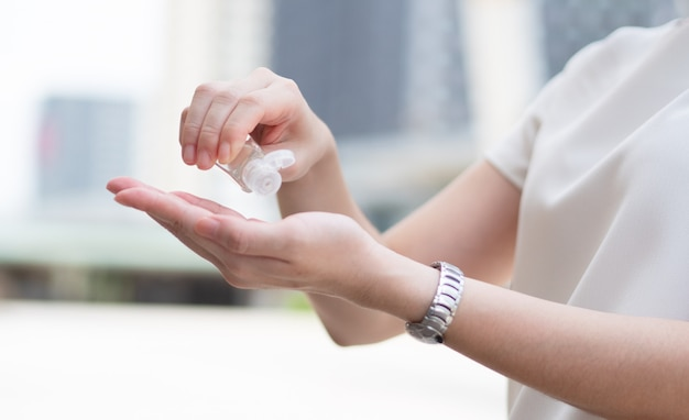 Hermosas mujeres asiáticas que usan mascarilla médica, usan gel de alcohol o desinfectante para limpiarse las manos mientras están en un área pública o centro de la ciudad, como una nueva tendencia normal