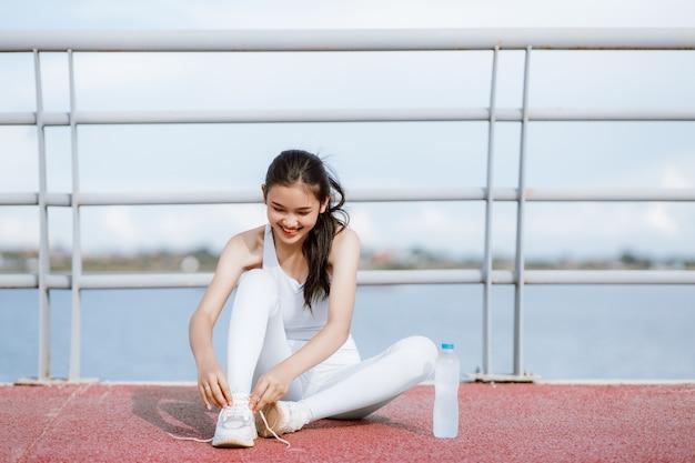 Hermosas mujeres asiáticas en ropa deportiva cuerpo de calentamiento para hacer ejercicio al aire libre. concepto de mujer sana. ejecución de entrenamiento.