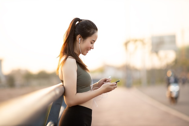 Hermosas mujeres asiáticas en ropa deportiva escuchar música durante el ejercicio al aire libre en el parque al atardecer. concepto de mujer sana.