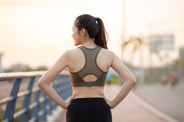 Hermosas mujeres asiáticas en ropa deportiva haciendo ejercicio al aire libre en el parque durante la puesta de sol. concepto de mujer sana.
