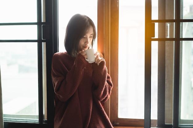 Hermosas mujeres bebiendo café caliente junto a la ventana en el dormitorio