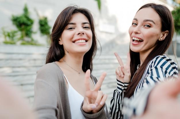 Hermosas mujeres casuales haciendo selfie al aire libre en la ciudad