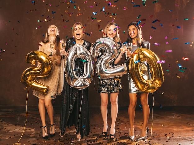 Hermosas mujeres celebrando el año nuevo. chicas hermosas felices en elegantes vestidos de fiesta sexy