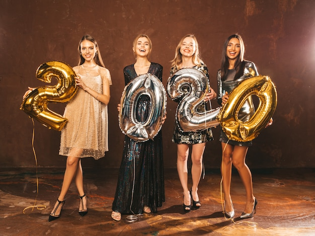 Hermosas mujeres celebrando año nuevo. niñas hermosas y felices con elegantes vestidos de fiesta sexys con globos dorados y plateados 2020, divirtiéndose en la fiesta de fin de año. celebración navideña modelos encantadores