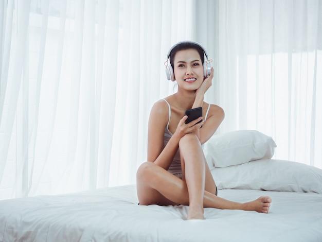 Hermosas mujeres escuchando música a través del teléfono en la cama