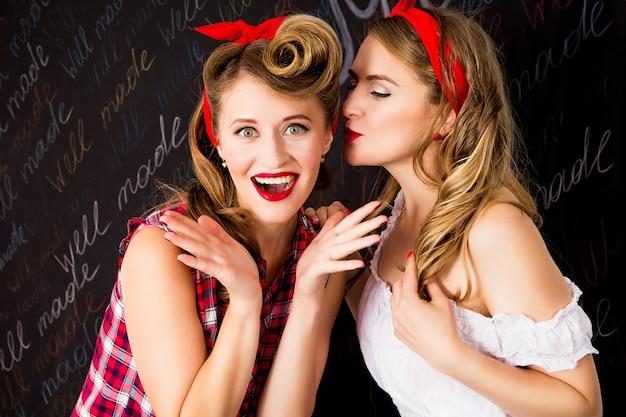 Hermosas mujeres hablando. chicas en estilo pin up con peinado y maquillaje perfectos