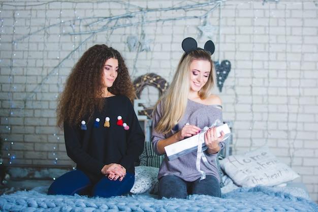 Hermosas mujeres jóvenes en celebración de navidad con regalos