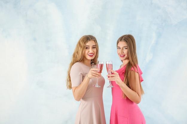 Hermosas mujeres jóvenes con copas de champán sobre fondo claro
