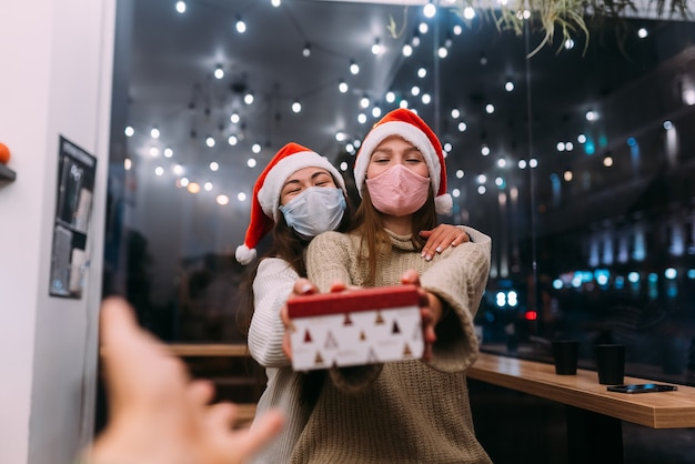 Hermosas mujeres jóvenes dan caja de regalo en el café