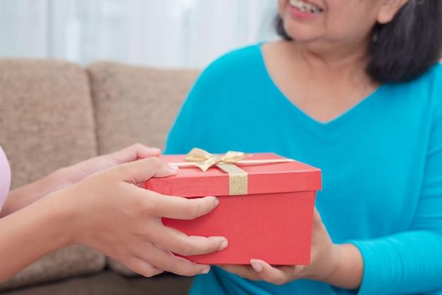 Hermosas mujeres jóvenes dan regalos a las madres.
