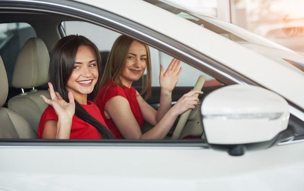 Hermosas mujeres jóvenes gemelas sentadas en los asientos del pasajero delantero y sonriendo mientras posan