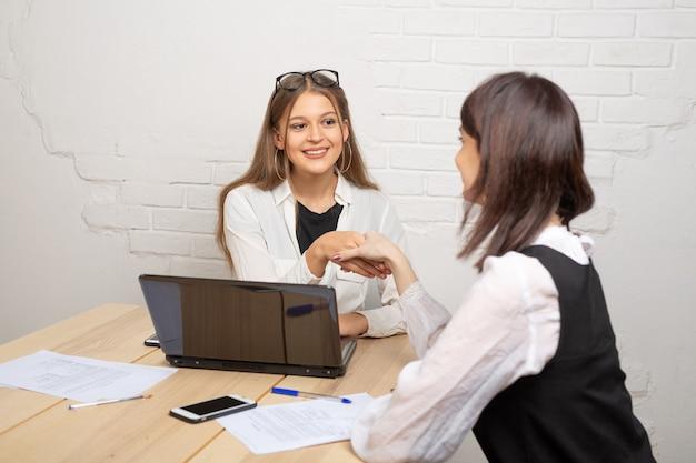 Hermosas mujeres jóvenes en la oficina dándose la mano