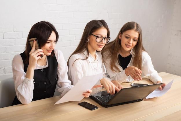 Hermosas mujeres jóvenes en la oficina con ordenador portátil