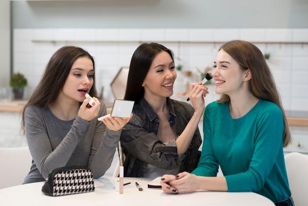 Hermosas mujeres jóvenes probando accesorios de maquillaje