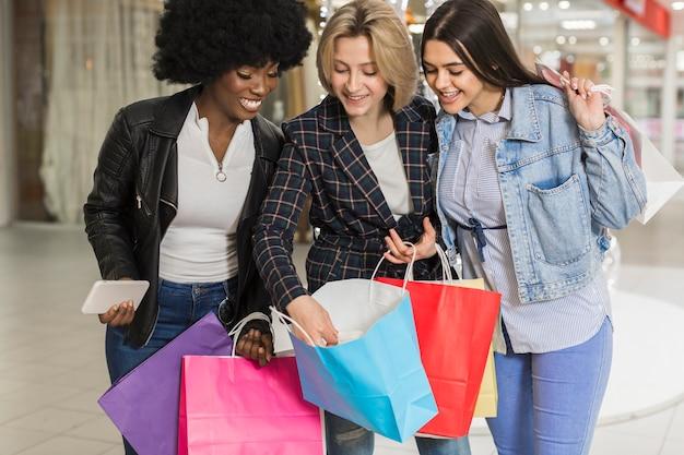 Hermosas mujeres jóvenes revisando bolsas de compras