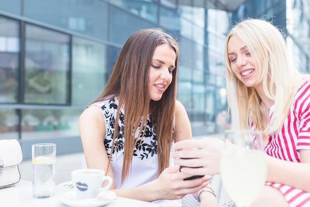 Hermosas mujeres jóvenes sentados en el café mirando el teléfono móvil