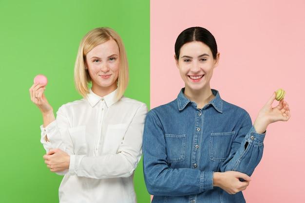 Hermosas mujeres jóvenes sosteniendo macarrones pastelería en sus manos