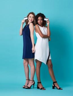 Hermosas mujeres jóvenes con tarjeta de crédito en azul