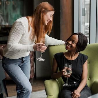 Hermosas mujeres jóvenes tomando vino juntos