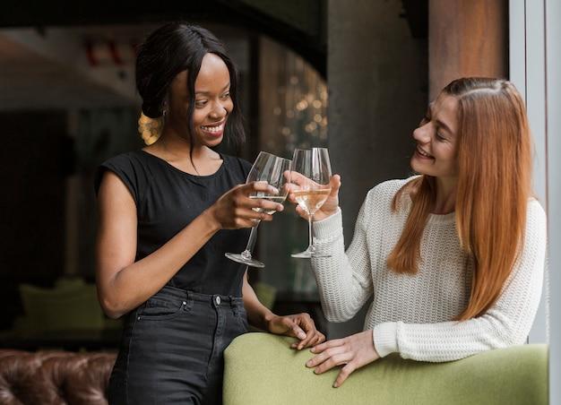 Hermosas mujeres jóvenes tostado copas de vino