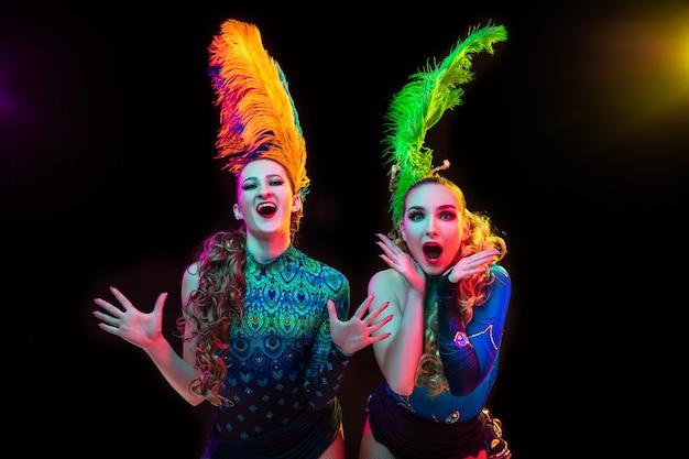 Hermosas mujeres jóvenes en traje de carnaval y mascarada en coloridas luces de neón en pared negra