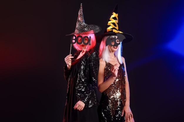 Hermosas mujeres jóvenes vestidas como brujas en la oscuridad. celebración de halloween