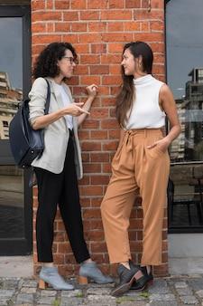 Hermosas mujeres de negocios hablando afuera