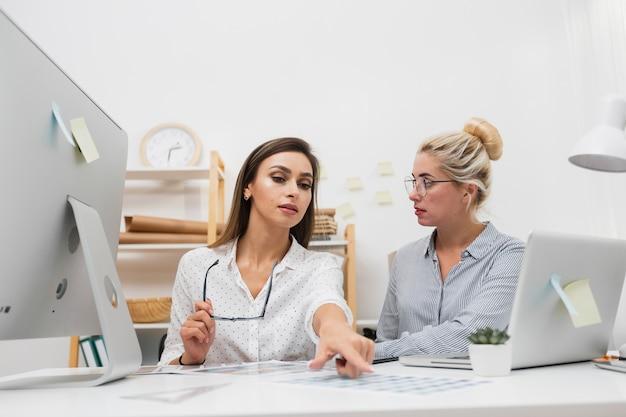 Hermosas mujeres de negocios sentado en la oficina