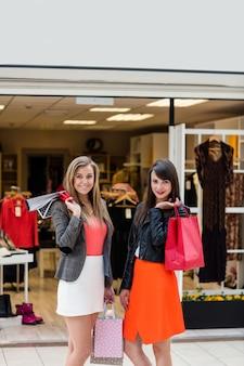 Hermosas mujeres de pie delante de la tienda de ropa