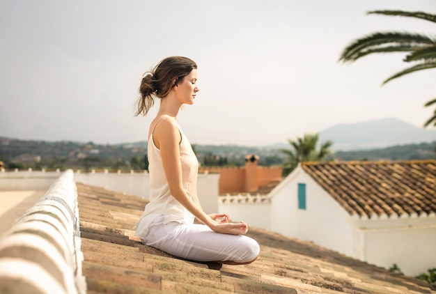 Hermosas mujeres practicando meditación, sentadas en una azotea