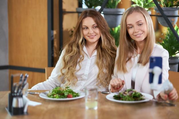Hermosas mujeres sentadas a la mesa con sabrosas ensaladas