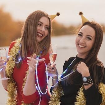 Hermosas mujeres sosteniendo copas de champán y lámparas en la fiesta en la azotea