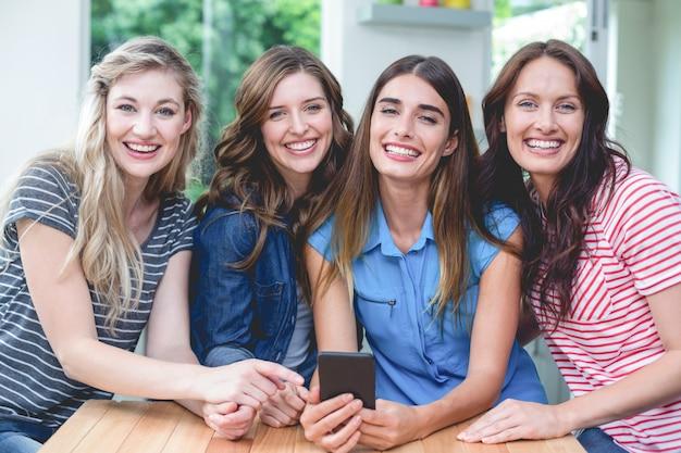 Hermosas mujeres sosteniendo un teléfono móvil