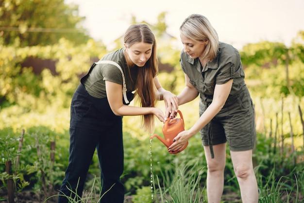 Hermosas mujeres trabajan en un jardín cerca de la casa.