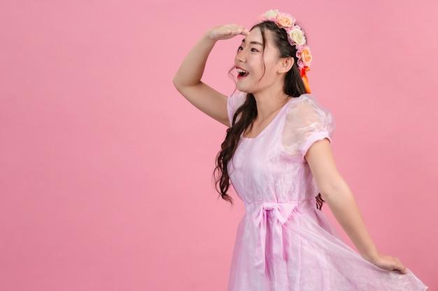 Hermosas mujeres vestidas con hermosos vestidos de princesa rosa están de pie sobre un rosa.