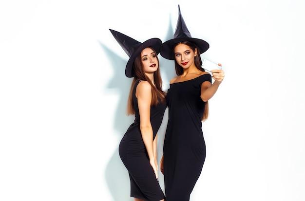 Hermosas mujeres vestidas con traje de bruja para la fiesta de halloween