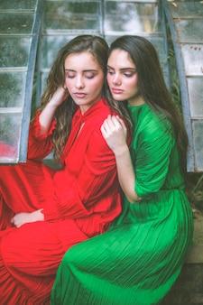 Hermosas mujeres en vestidos mirando hacia abajo