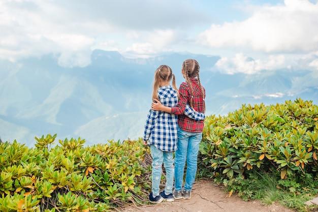 Hermosas niñas felices en las montañas en el fondo de niebla