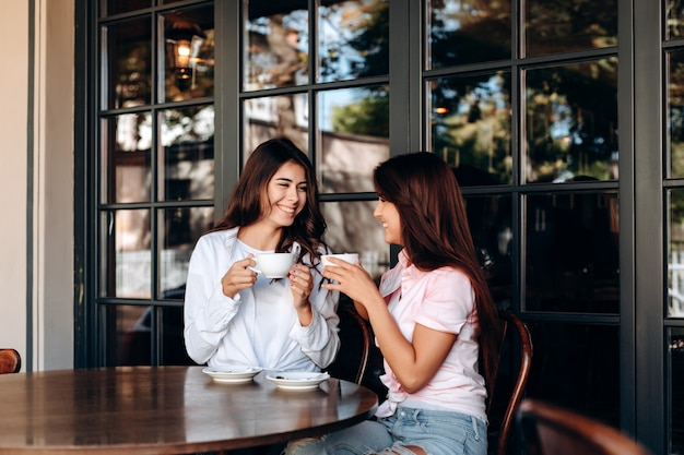 Hermosas novias divertirse en la cafetería