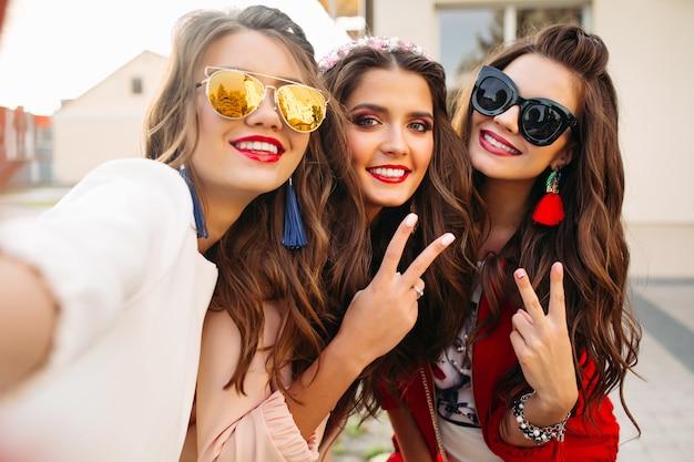 Hermosas novias en gafas de sol que muestran signos de paz