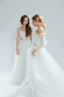 Hermosas novias con maquillaje y peinado de novia y largos vestidos blancos