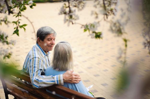 Hermosas personas mayores felices sentados en el parque otoño